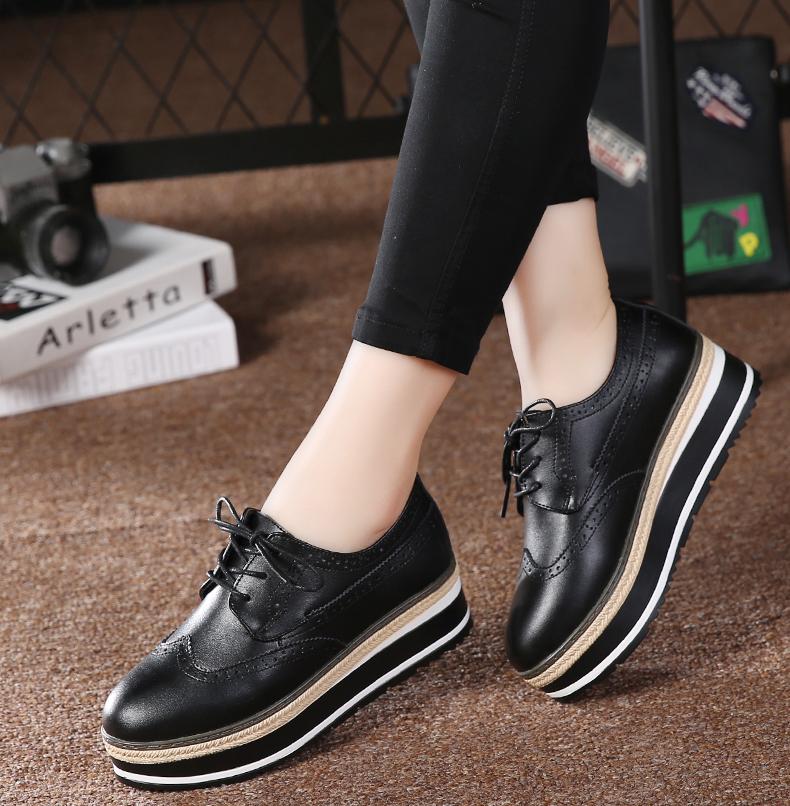 Giày thể thao nữ đế cao bằng da , màu đen trơn bóng .